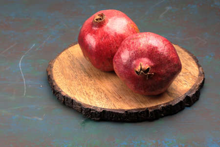 Red Pommegranate on a wooden background with copy space.