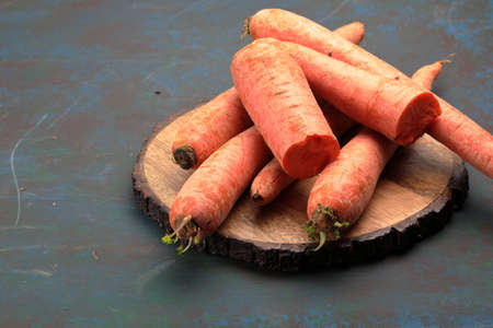 A stack of orange Carrots on a wooden background with accomodation for copy space. Stock Photo