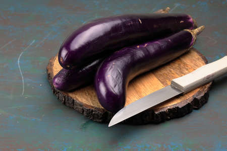 A container with long purple Chinese Eggplants or Brinjal on wooden background with copy space. Stock Photo