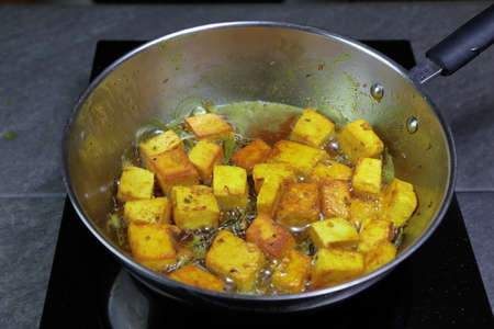 Cooking and frying Paneer or Tofu in oil with Turmeric and green chilies on an induction stove. Stok Fotoğraf