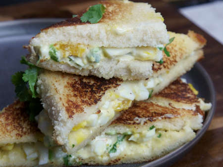 A stack of Bread and egg salad with mayonaise sandwich on a plate with copy space.