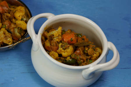 Mixed vegetable curry in a dish on a wooden blue background, with copy space.