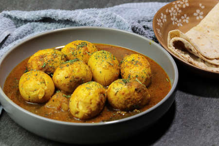 An Indian spread of spicy Egg curry or Egg Masala in a bowl on a stone bckground.