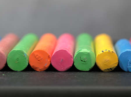 A row of colorful chalks on grey background.