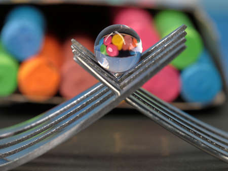 A still life of small transparent balls on forks with a reflection of colored chalks. Macro image.