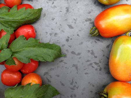 Cherry tomatoes with Roma Tomatoes on a grey background with copy space.