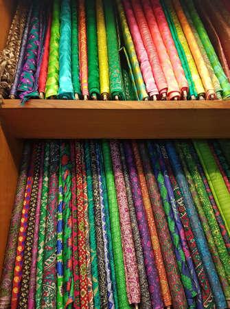 tela seda: Vibrantes colores con textura rollos de tela de seda finos apilados en estantes de madera