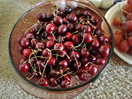 Glass bowl of Fresh produce Red cherries with cherry grapes Stock Photo