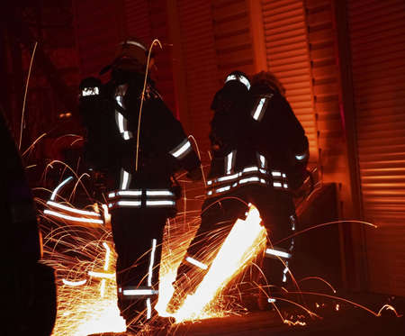 Notte vigili del fuoco; taglio una porta  Archivio Fotografico - 3595638