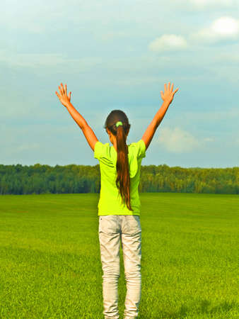 preteen  pure: Joyful preteen girl in green field Stock Photo
