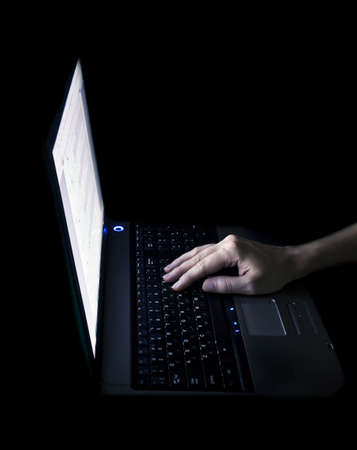 hand typing on laptop, in black photo