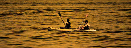 Paired canoeing at sunset photo