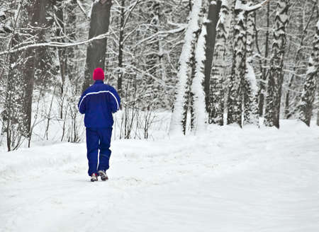 wintry: lone runner in wintry wood Stock Photo
