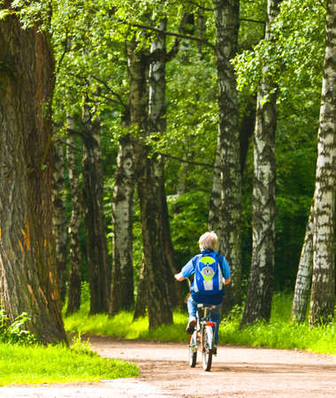 knapsack: young bicyclist in forest