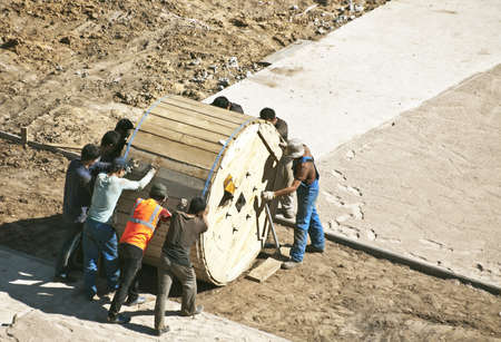 ponderous: builders pushing the cable bobbin  Stock Photo