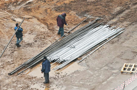 unloading the metal pipes photo