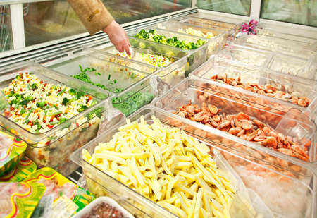 refrigerator with food: prepared vegetables and seafoods in shop-freezer