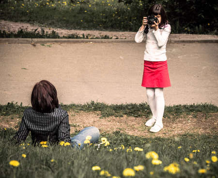 urban parenting: daughter photographing mother outdoor