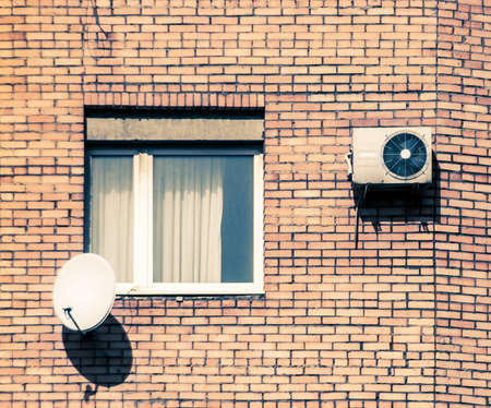 habitable: window with conditioner and dish-antenna Stock Photo