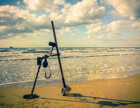 metal detector and sand scoop on the beach (changes)