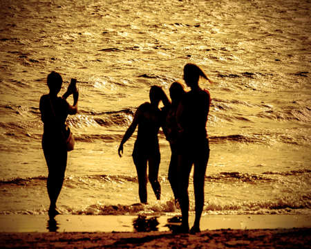 girls take photographs in the beach