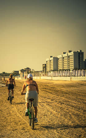 older women ride bikes along beach
