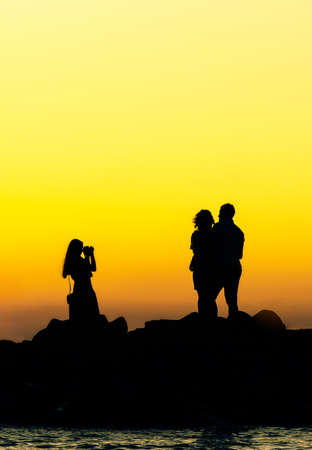 couple are photographing on sunset rocks