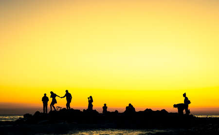 people at the sunset rocky shore