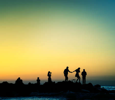 various people at sunset rocky shore