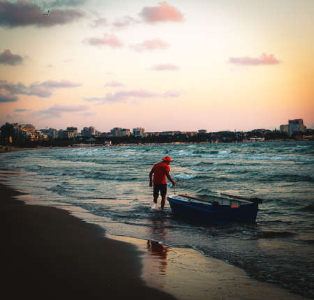 Anapa, Russia, 2020: beach lifeguard stands in stormy surf with his rowing boat at evening