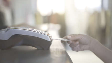 Close up of woman s hand paying with a credit card in a store and taking her purchase. Consummer