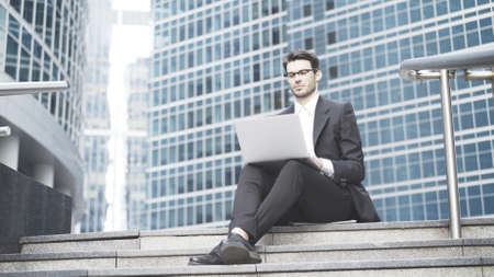 A young prospective business man in a black suit working in the open-air with a laptop. A big city and downtown on the background, sitting on the stairs Stock Photo