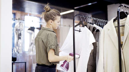 A young blonde girl worker in a clothing store shope is steaming clothes a white shirt in a market place Zdjęcie Seryjne