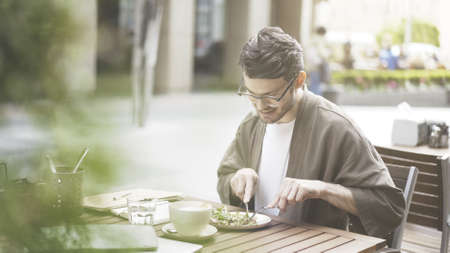A handsome bearded man in eyeglasses eating fresh salad at cafe outdoors alone Stock Photo - 101153733