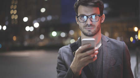 A confident young looking at the camera holding scrolling texting in his cellphone. A man calls for a taxi in an app.