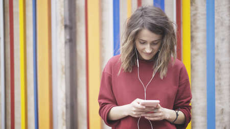 A portrait of young girl dressed in a red sweatshirt listens to music in earphones looking at her phone on the cloured background
