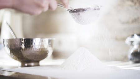 A closeup of a woman sifting a flour through a little sieve. A woman holding a little sieve to sift a flour