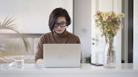 Pan shot right to left of smiling asian woman in eyeglasses working with laptop. Glass of water on table and a vase with flowers in white interior home office
