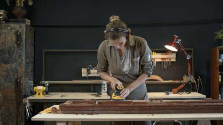 Young woman grinds the wooden door, restoration works. Female wearing hearing protection device grinding, polishing old door in workshop Reklamní fotografie