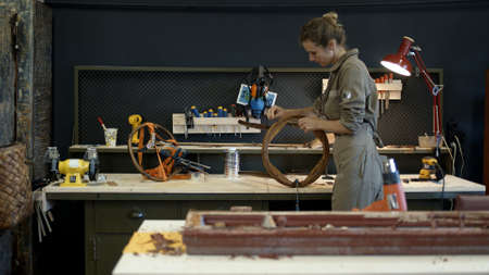 Restoration of wooden chair in a workshop. A working female carpenter peels off paint from a wooden product with a spatula, restorer in a workshop, gimbal shot