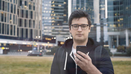 Man in eyeglasses holding a phone on background of business centre. Man dressed in casual clothes texting in the phone wearing a black hoodie