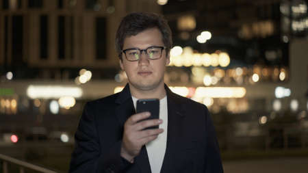 Businessman in eyeglasses texting on the phone on background of building with yellow lights, bokeh effect. Night shot man in black jacket texting near the road.