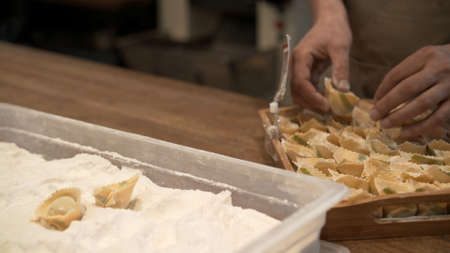 Male hands in flour on several ravioli in the tray with flour. Preparation of italian food at the restaurant kitchen, cook laying italian ravioli on wooden tray Stock fotó - 155451115