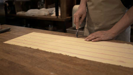 Male hands cutting dough rolled on big wooden table at the restaurant kitchen. Making ravioli, cutting big long slice of raw dough, italian cuisine Stock fotó