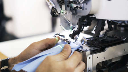 Sewing on machine and green laser, needle and hands with and blue cloth close up. Sewing process, female hands getting blue cloth to a modern white machine