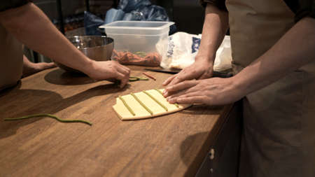 Male hands preparing italian food, process of ravioli making at the restaurant kitchen. Dough and ingredients for ravioli preparation, middle shot no face Stock fotó