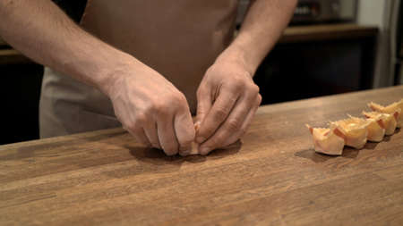 Cook preparing ravioli, rolling dough with stuffing on wooden kitchen table. Male hands cooking italian food, handmade ravioli at the restaurant kitchen