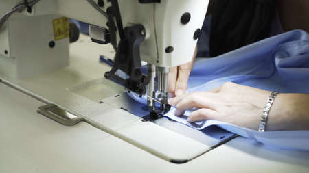 Sewing on machine, hands and blue cloth close up. Sewing process, female hands on white machine, blue shirt on table with white sewing machine Stock fotó - 155451512