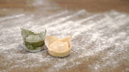 Two raw italian green, white tortellini on wooden table, italian flag colors. Close up of raw italian tortellini with flour on restaurant kitchen table