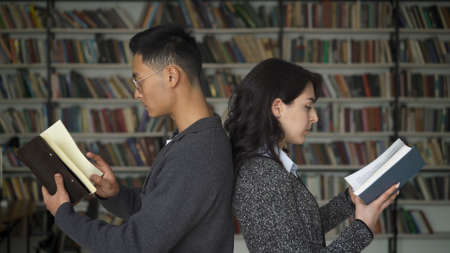 Female and male standing back to back reading books, on background of bookshelves. Young couple man and woman on background of large bookshelves Stock fotó - 157496246